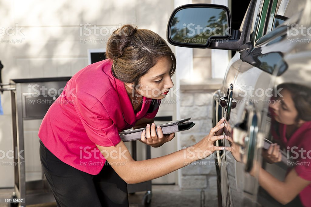 Automobile insurance adjuster inspecting damage to vehicle royalty-free stock photo