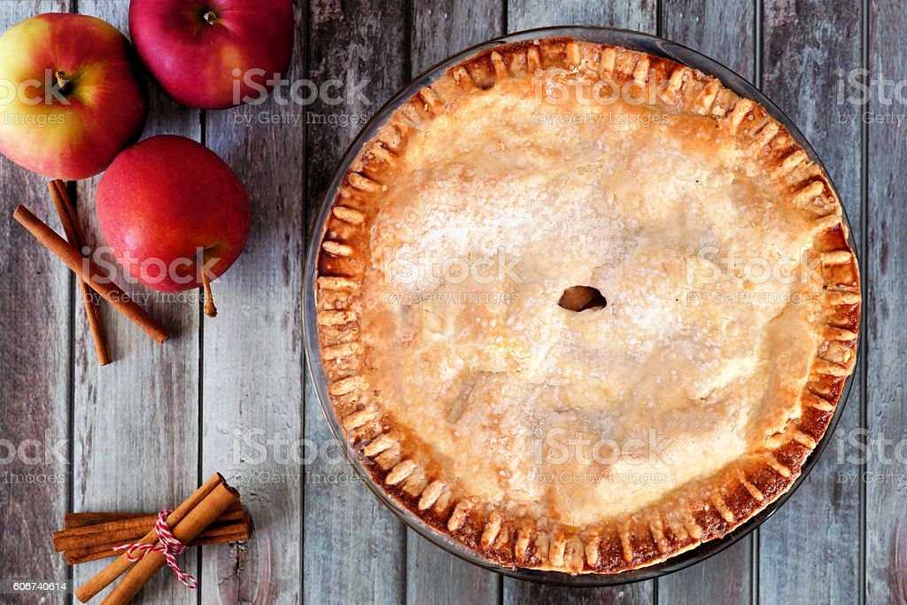 Autumn apple pie, overhead table scene over rustic wood stock photo