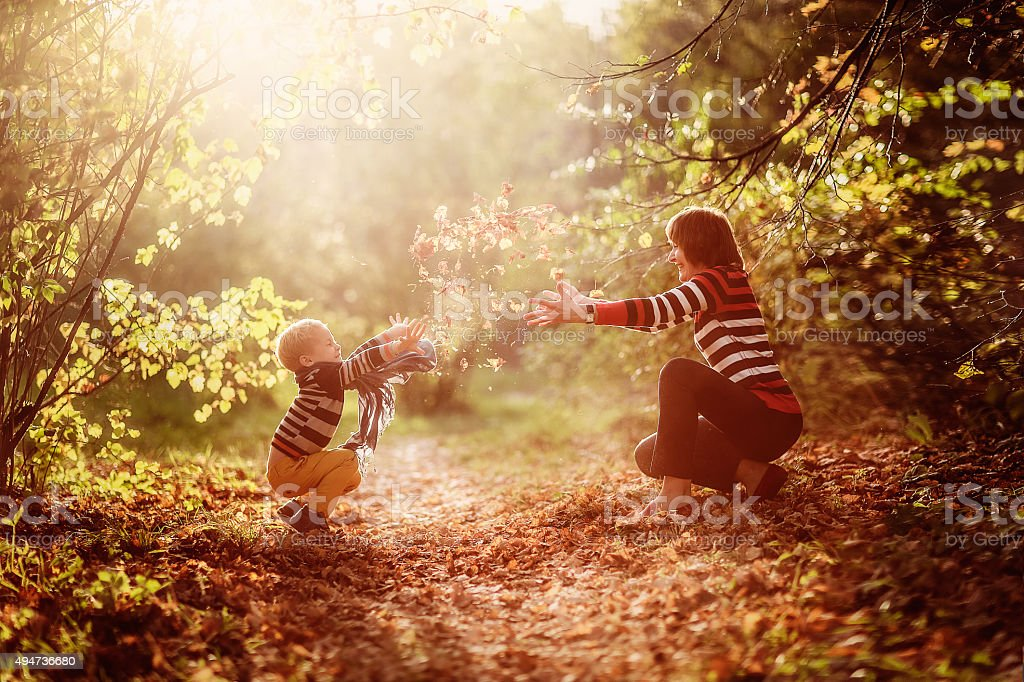 autumn baby boy and his mother throwing yellow leaves stock photo