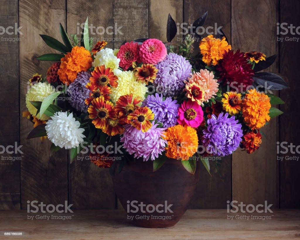 Autumn bouquet of garden flowers on wooden background. stock photo