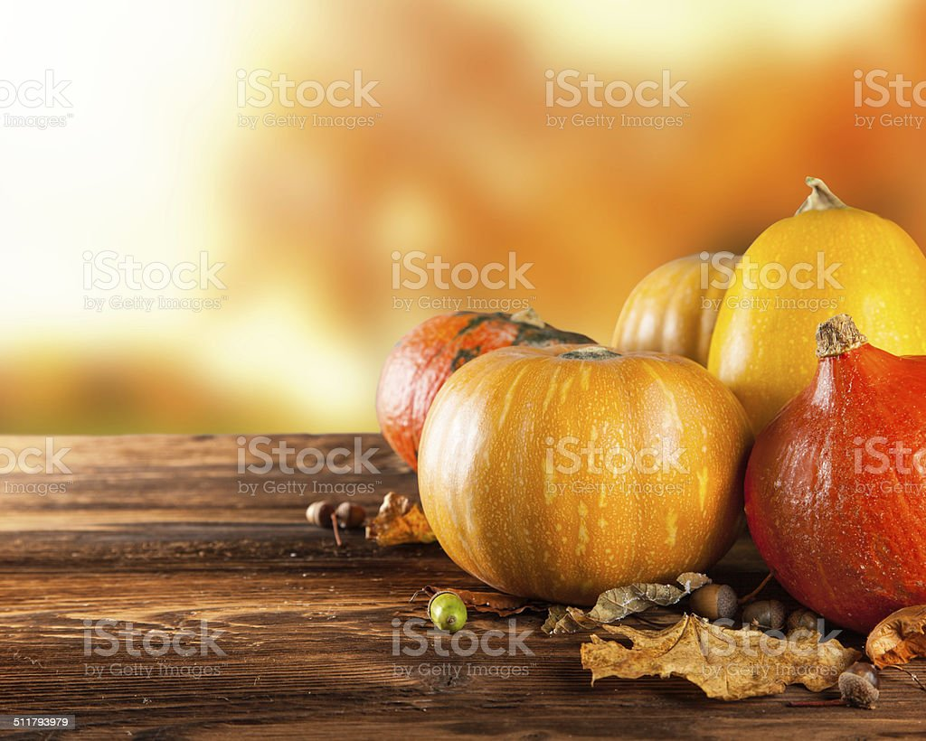 Autumn colored pumpkins on wooden table stock photo