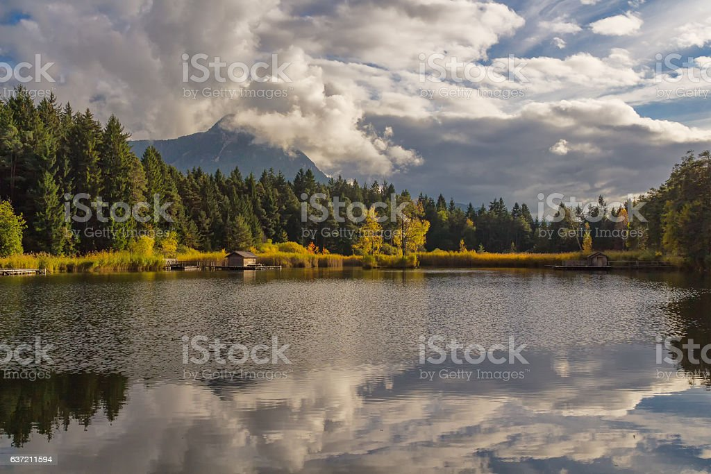 autumn colorful dolomites mountain peaks with blue sky reflecting in stock photo