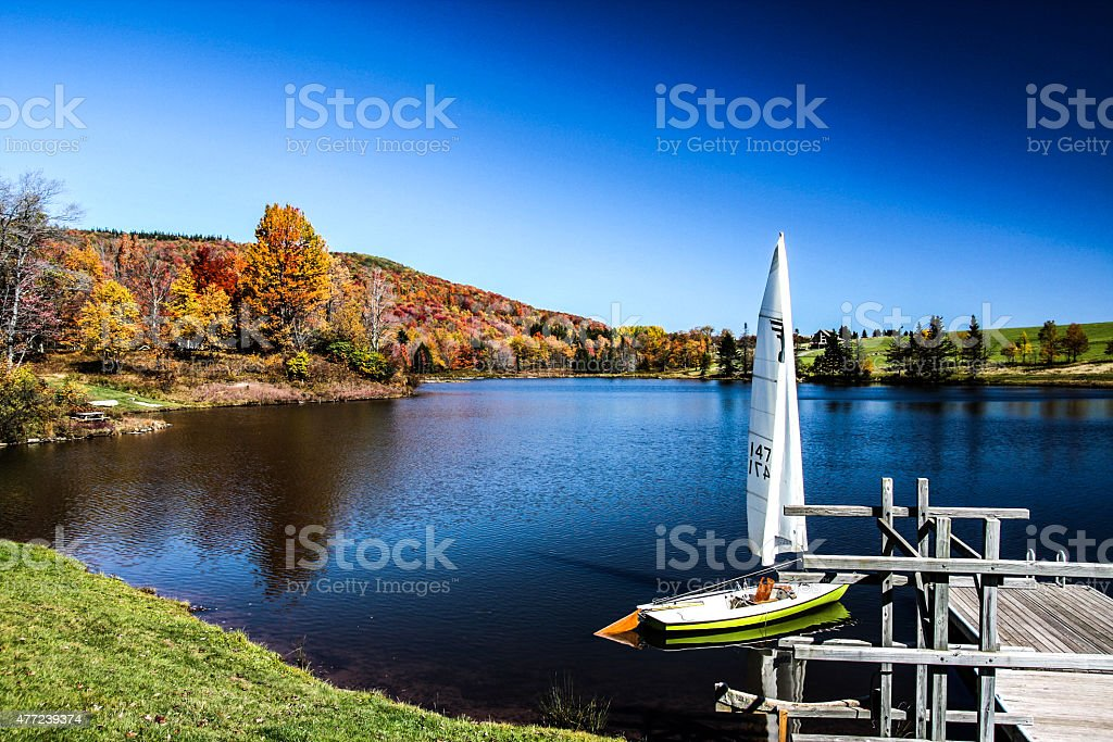 Autumn Colors and a lake with a sail boat and a dock stock photo