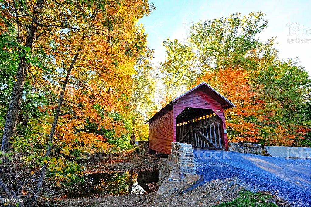 Autumn colors frame a covered bridge in Maryland stock photo