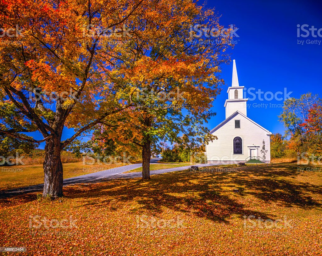 Autumn country side with white village church, VT stock photo