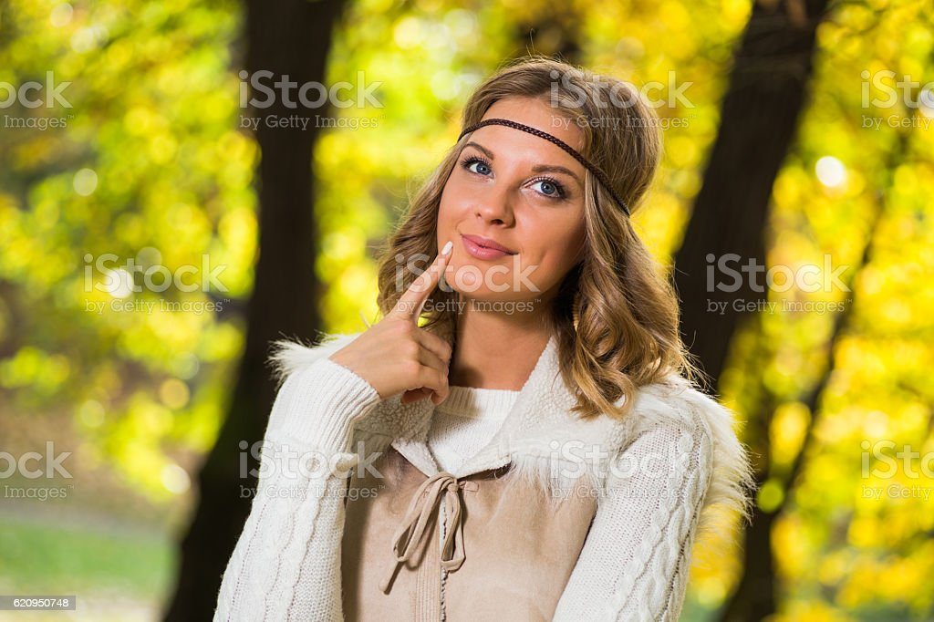 Beautiful boho girl enjoys in autumn day dreaming at the park.