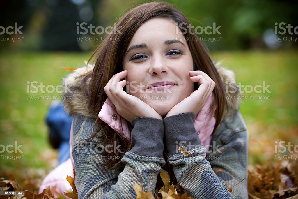 Autumn Day with Happy Young Latina Lying on Leaves royalty-free stock photo