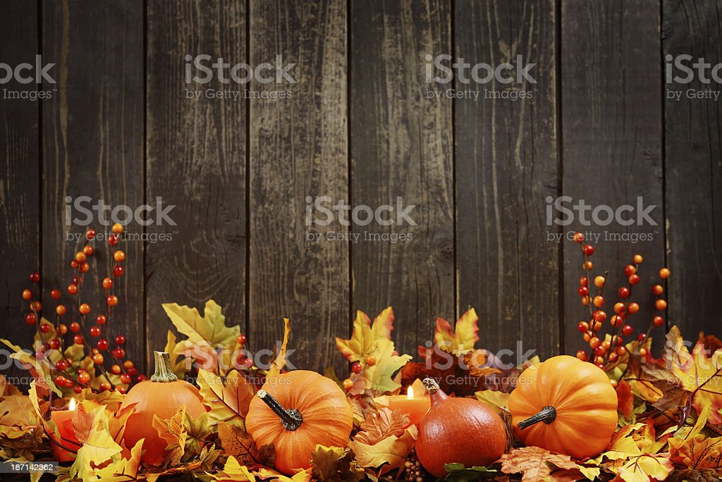Autumn decoration with maple leaves and pumpkins on old woods stock photo