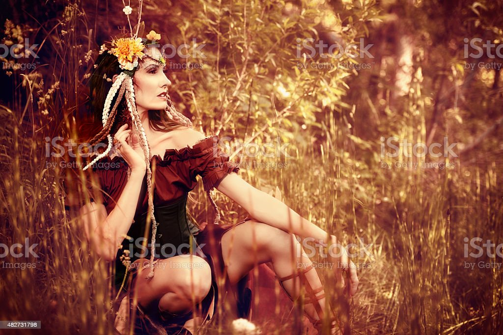 Autumn Fairy Queen Sitting In Her Explosion of Color stock photo