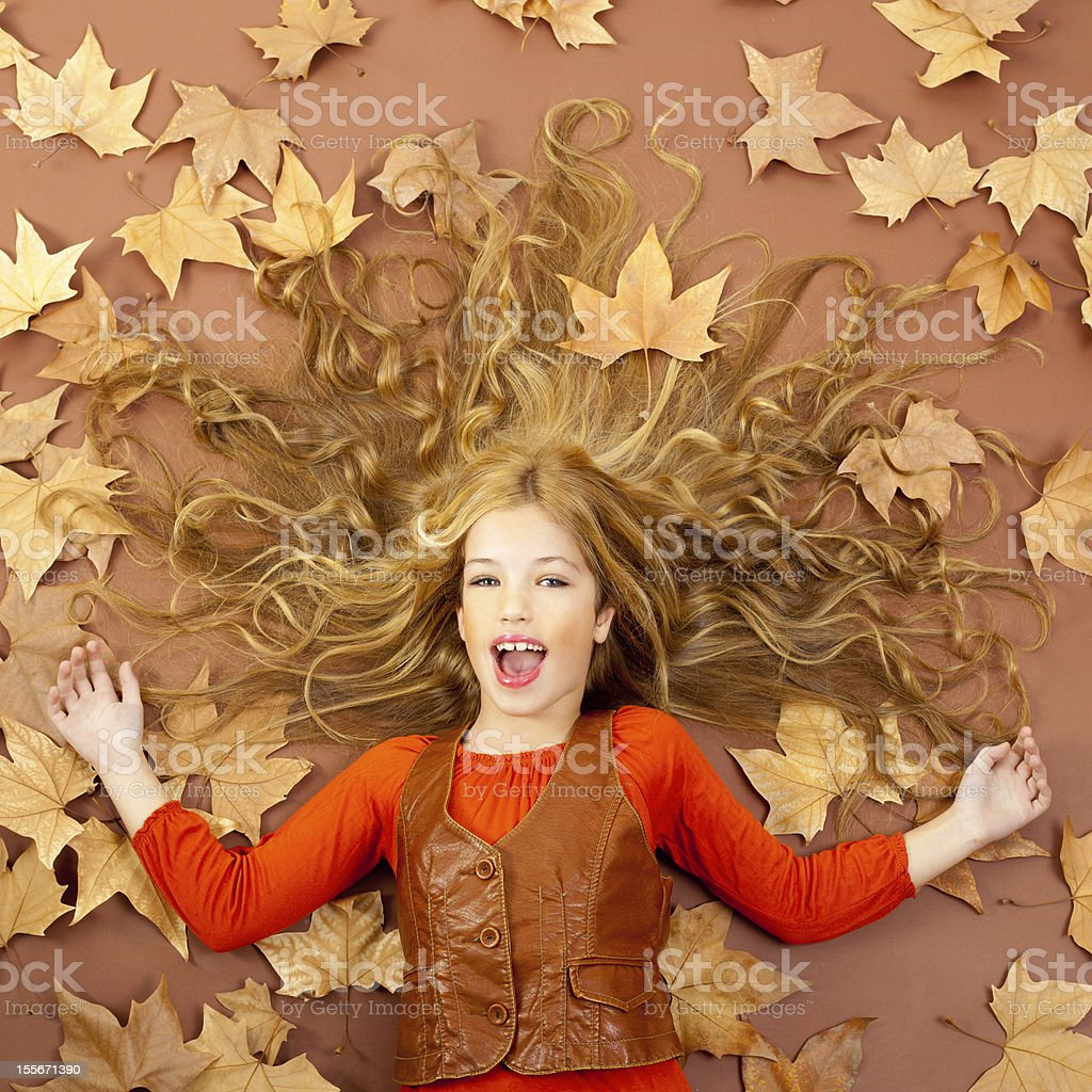 autumn fall little blond girl on dried tree leaves royalty-free stock photo