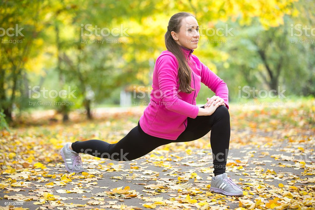Autumn fitness outdoors: high lunge exercises stock photo