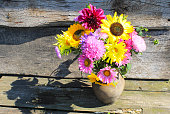Autumn flowers in rustic clay jug on wooden background