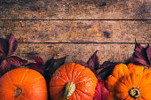 autumn food background with pumpkins and colored leaves