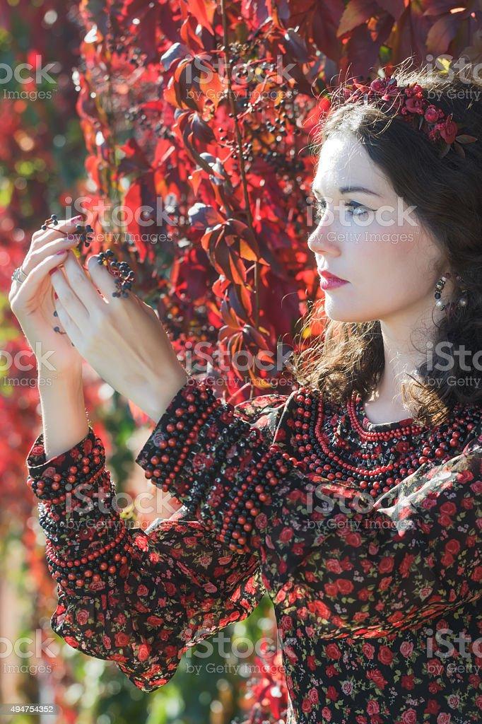 Autumn girl in autumn wreath with grape woodbine bunch stock photo