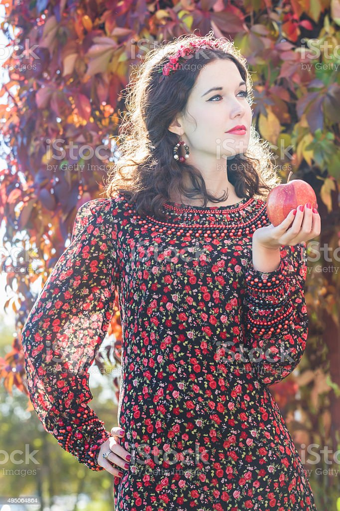 Autumn girl in fall wreath with red apple in arm stock photo