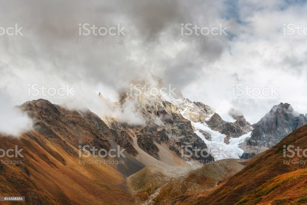 Autumn landscape and snow mountains in beautiful cumulus clouds. stock photo