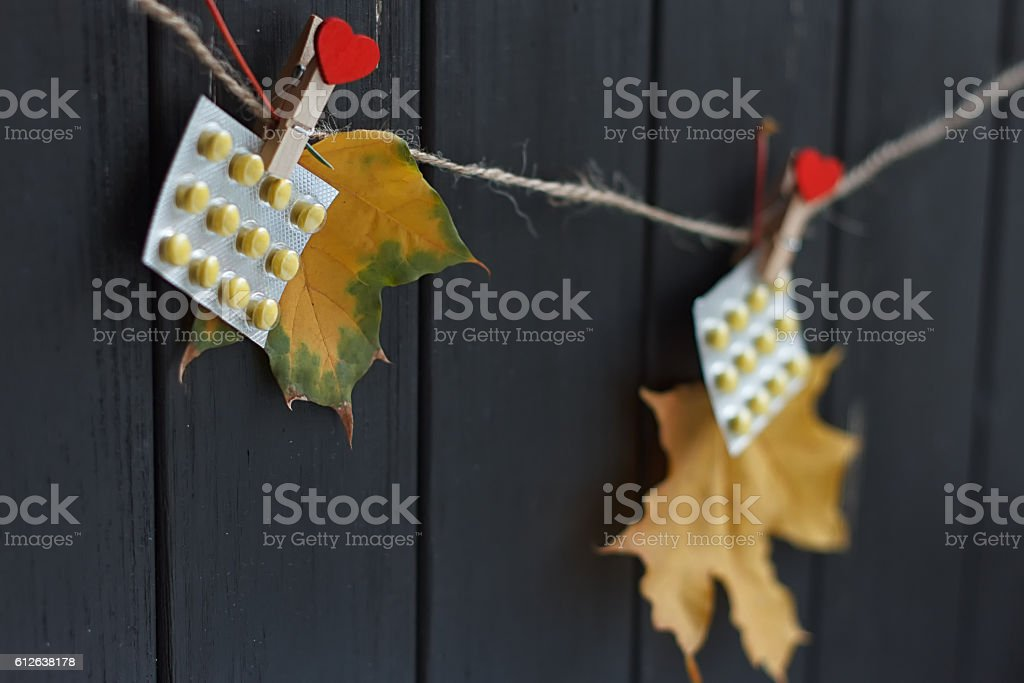 autumn leaves and pills on clothespins hanging stock photo