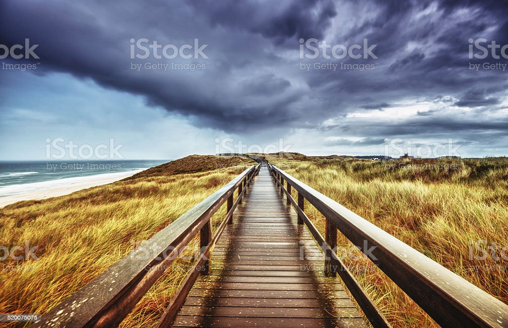 Autumn on Sylt - Wooden path under dramatic sky stock photo