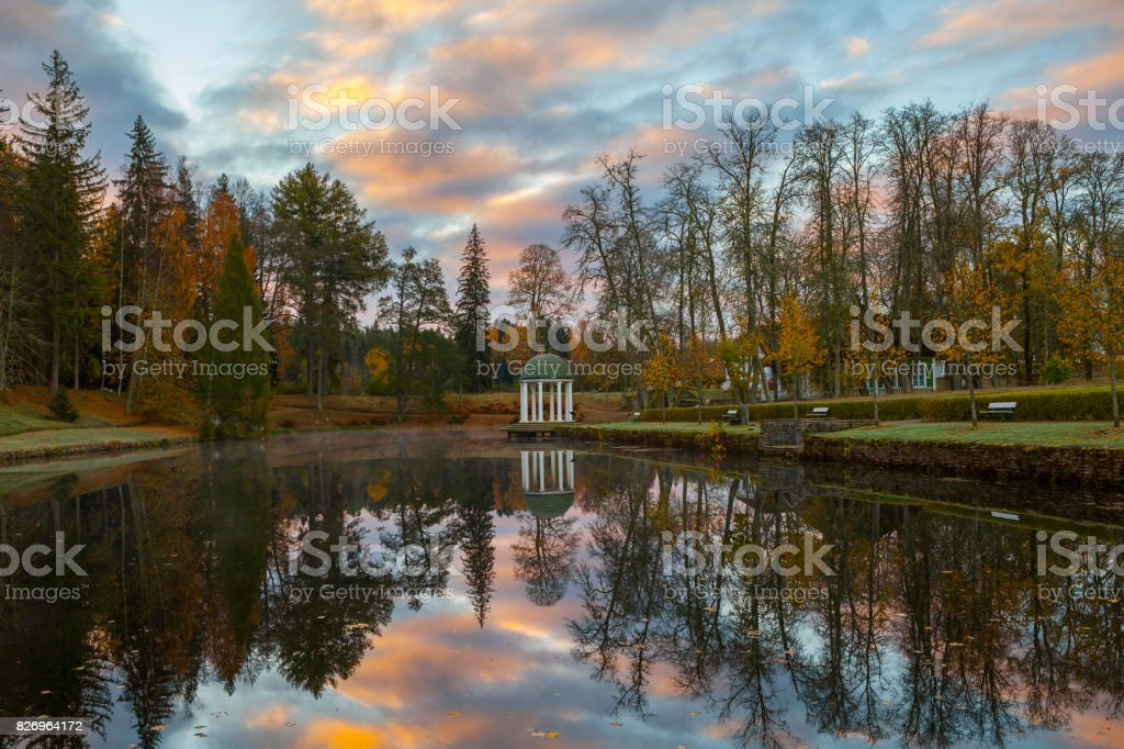 Autumn park around a pond with a rotunda. October fall time. stock photo