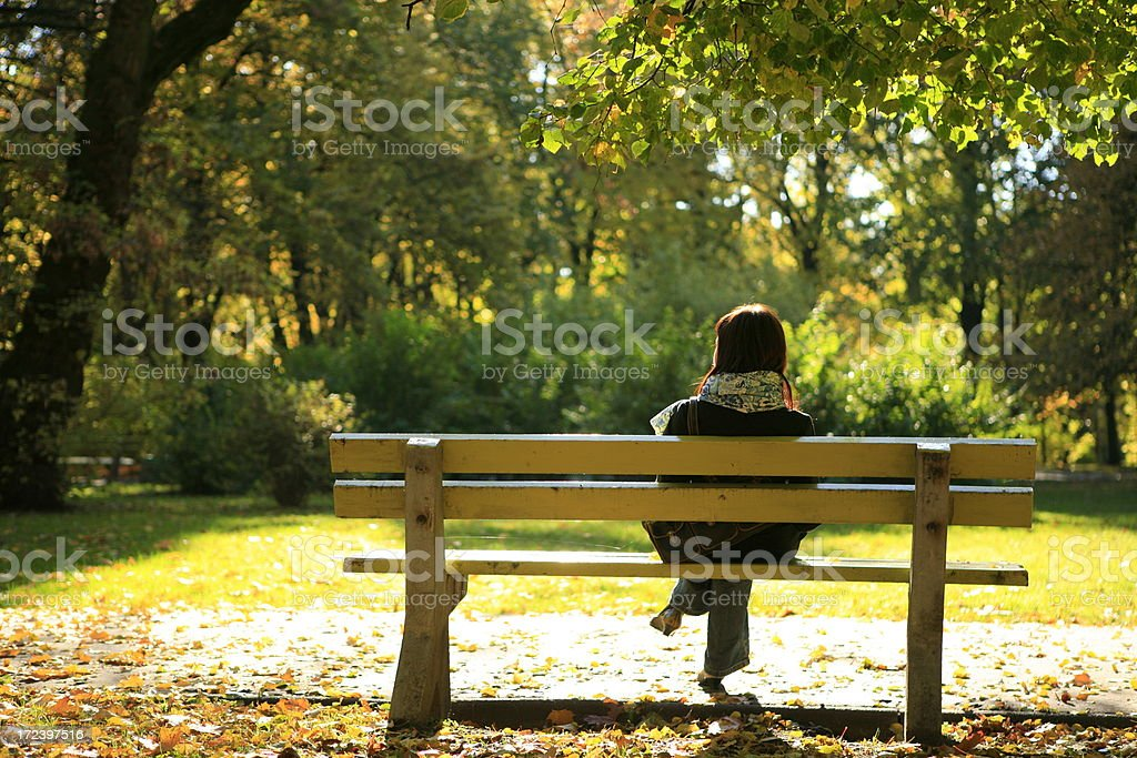 autumn park landscape with alone girl sitting royalty-free stock photo