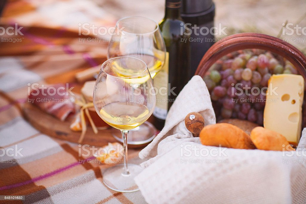 Autumn picnic by the sea with wine, grapes, bread, cheese stock photo