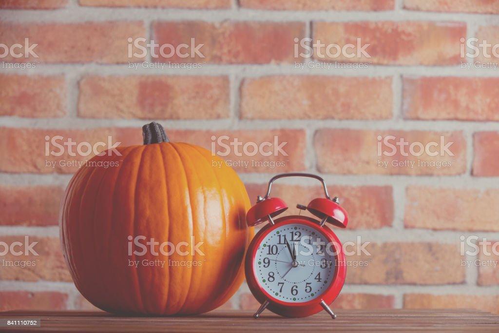 Autumn pumpkin and alarm clock stock photo
