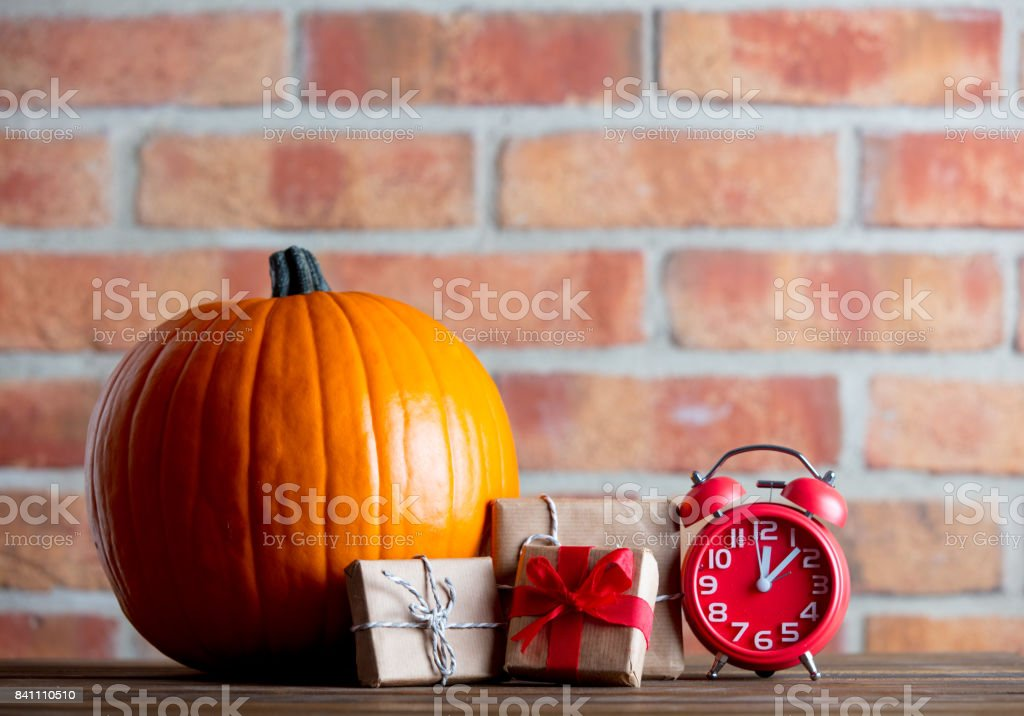 Autumn pumpkin and alarm clock with gifts stock photo