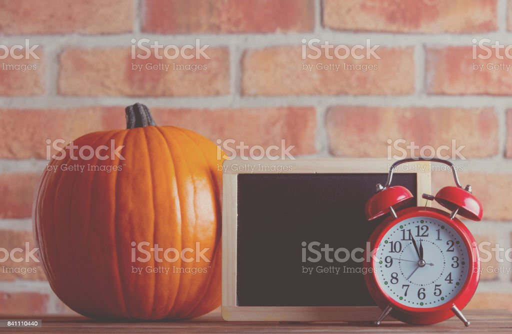 Autumn pumpkin and blackboard menu with alarm clock stock photo