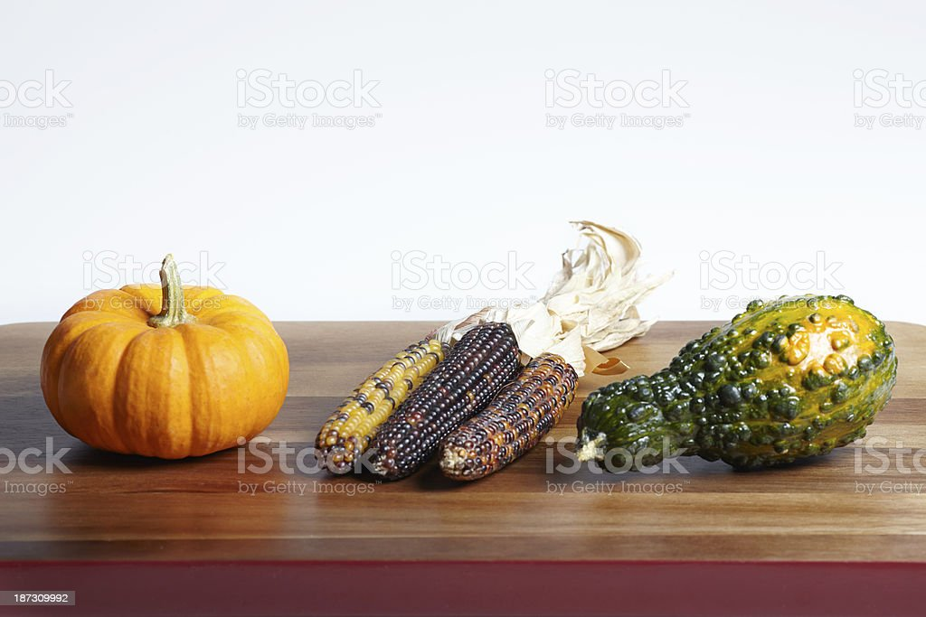 Autumn pumpkins variety and corns in a row on wood stock photo