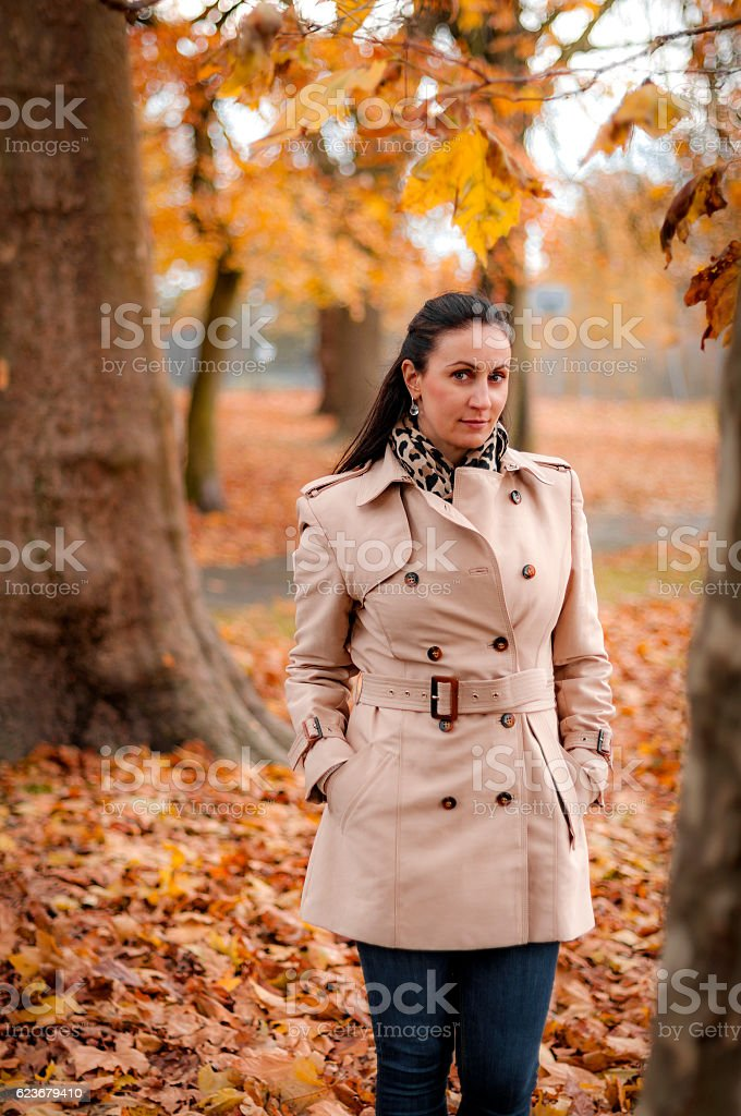 Autumn scene with woman in trenchcoat in the woods stock photo
