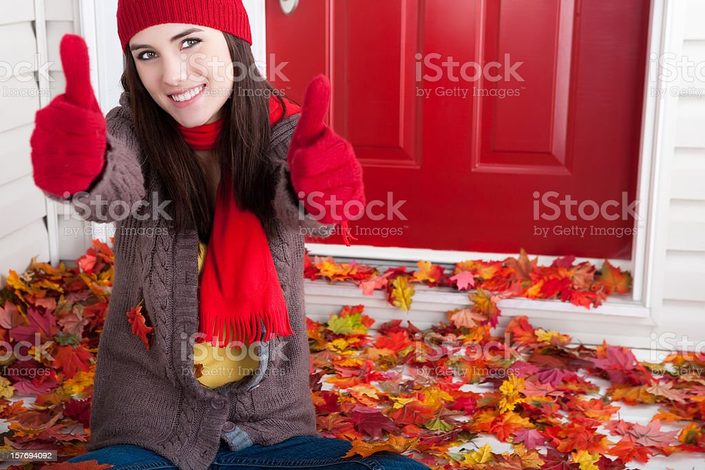 Autumn: Smiling young female with thumbs up royalty-free stock photo
