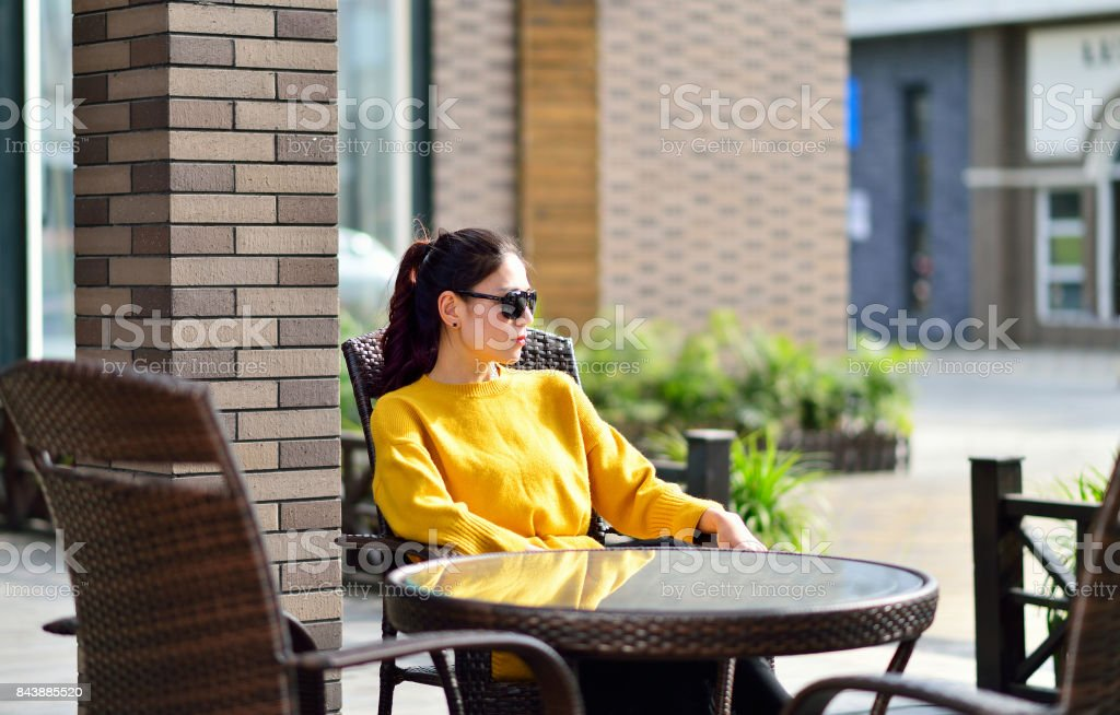Autumn, street cafe sat a woman wearing a sweater stock photo