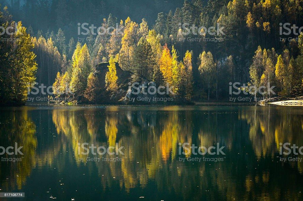 Autumn trees reflected on still black lake stock photo
