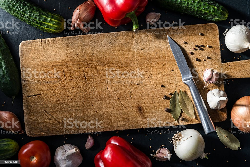 Autumn vegetables, spices on old wooden cutting board, stone table stock photo