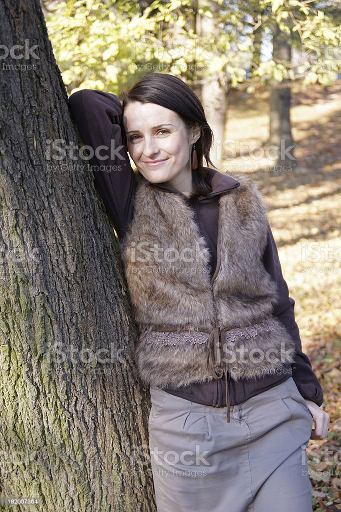 Autumn woman leaning tree royalty-free stock photo