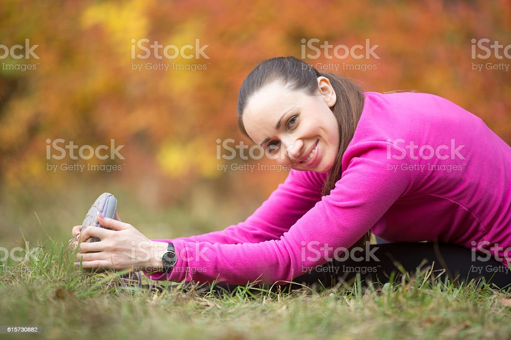 Autumn yoga: Seated Hamstring Stretch pose stock photo