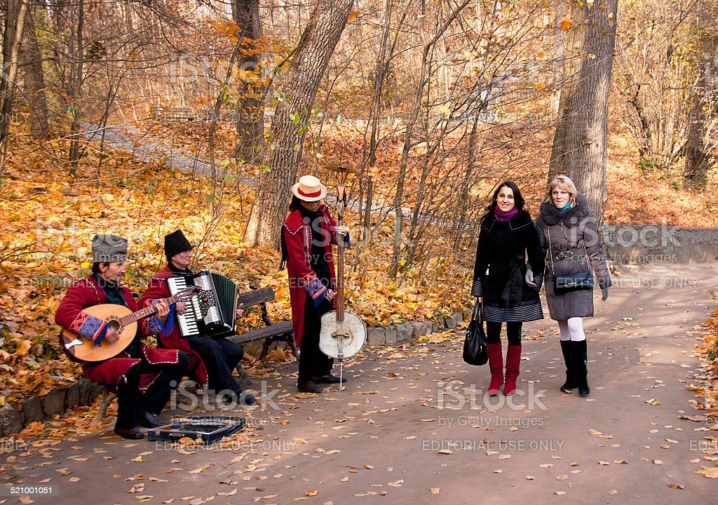 Autumnal view of Sofiivka park with girls and musicians. stock photo