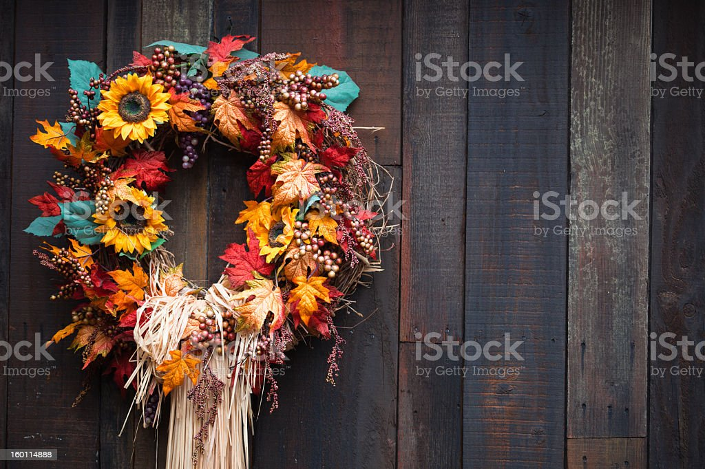 Autumnal wreath with sunflowers and leaves on wooden surface stock photo