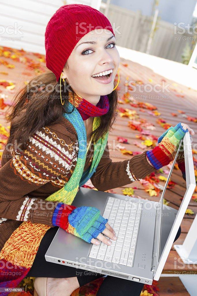 Autumn-Smiling woman using laptop outdoor royalty-free stock photo