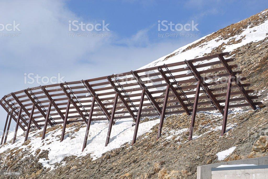 avalanche protection on mountain peak stock photo
