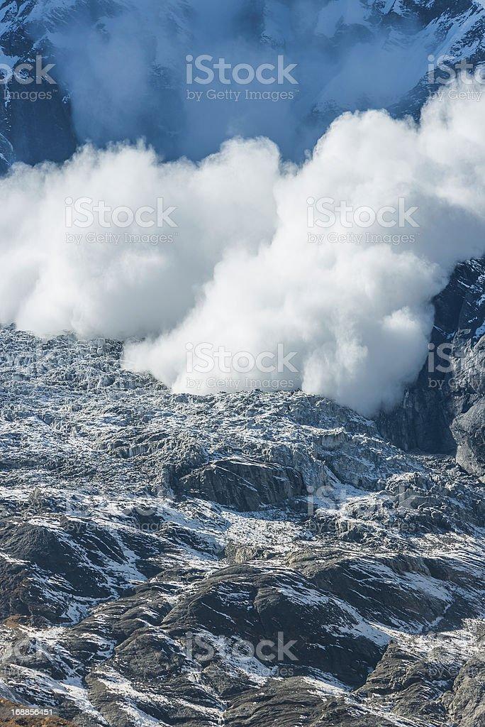 Avalanche snowfall cascading down mountain onto glacier stock photo