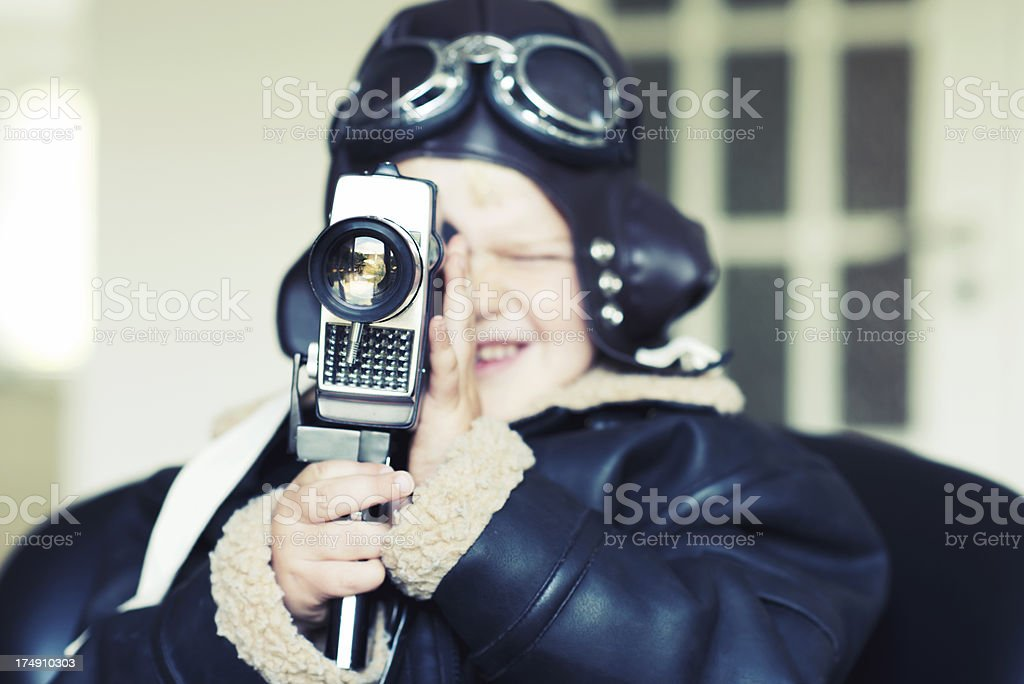 Aviator boy makes a movie with an old camera royalty-free stock photo