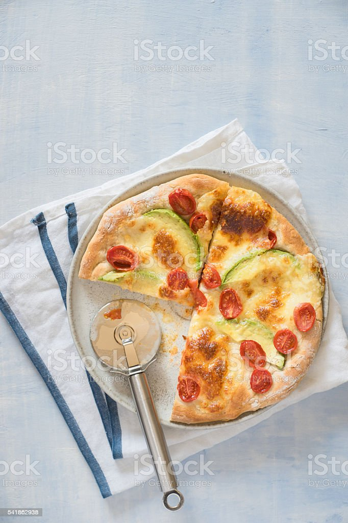 Avocado and cherry tomatoes pizza and pizza cutter stock photo