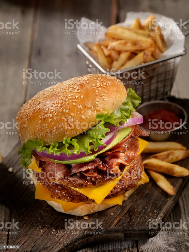 Avocado Bacon Cheeseburger with a Basket of Fries stock photo