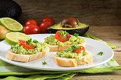 avocado cream or guacamole on baguette sandwiches, dark wood
