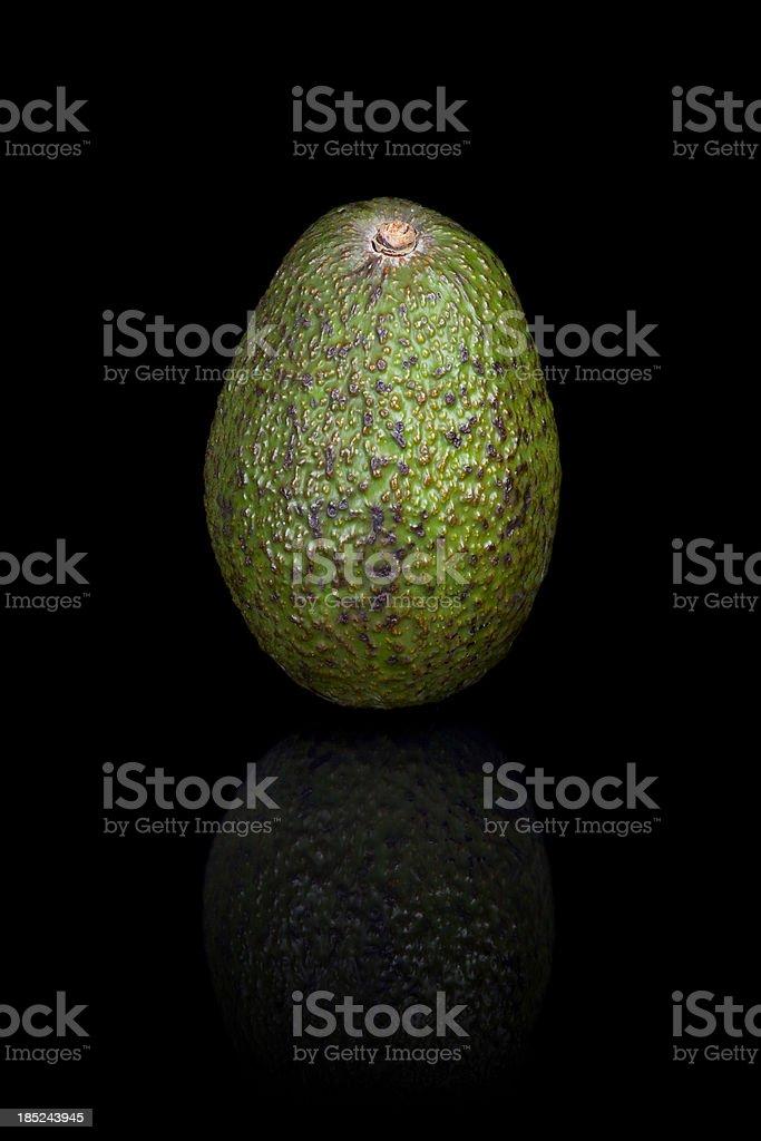 Avocado on a black reflective background royalty-free stock photo