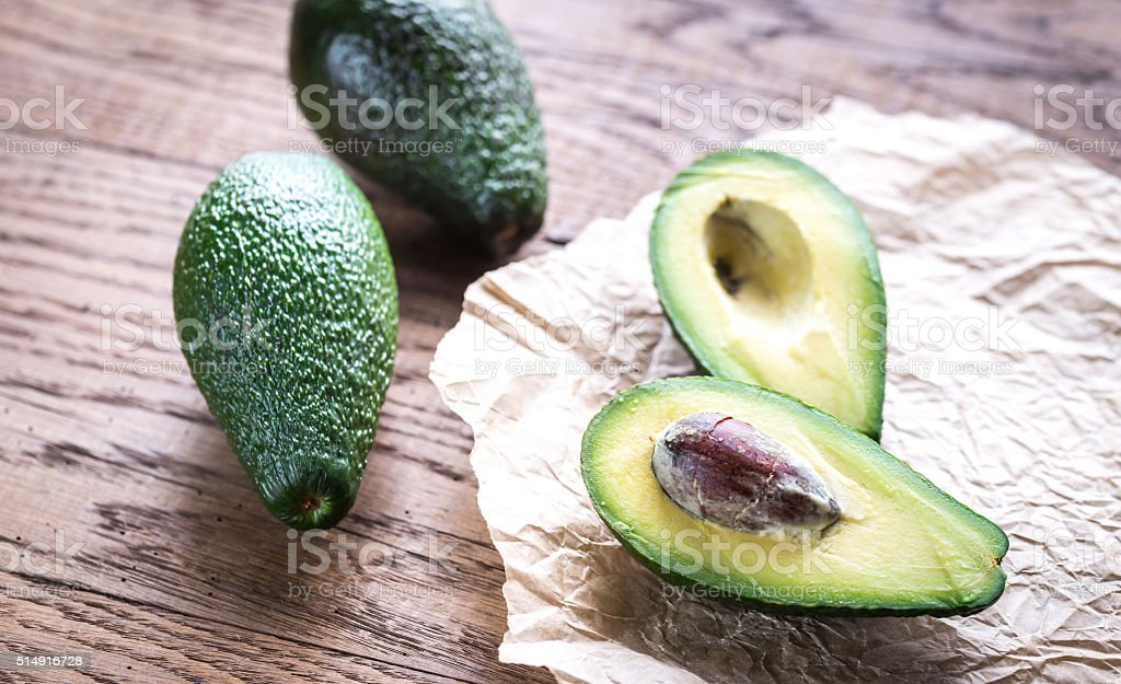 Avocado on the wooden background stock photo