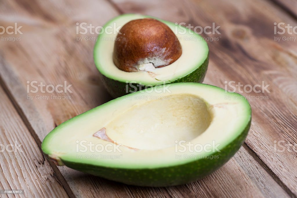 Avocado on wooden table stock photo