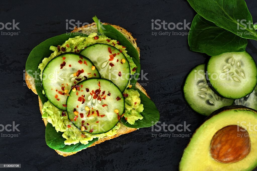 Avocado sandwich with cucumber and spinach on dark slate background stock photo