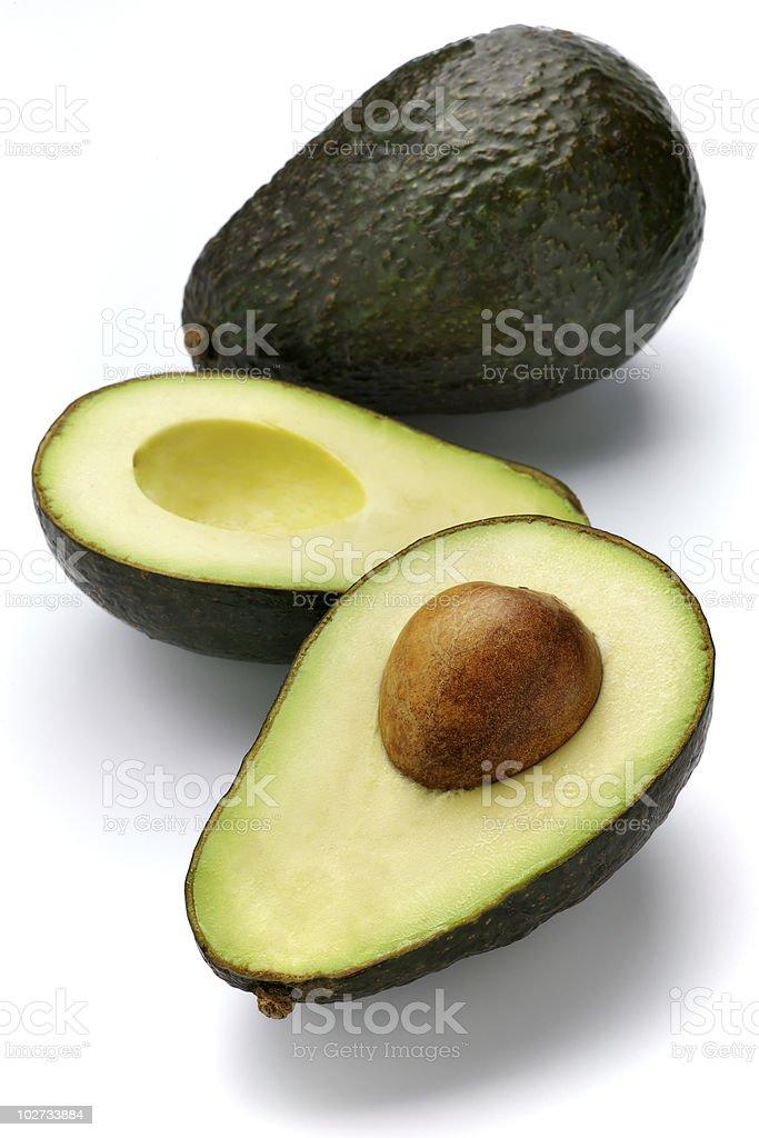 Avocado split in half with pit still inside royalty-free stock photo